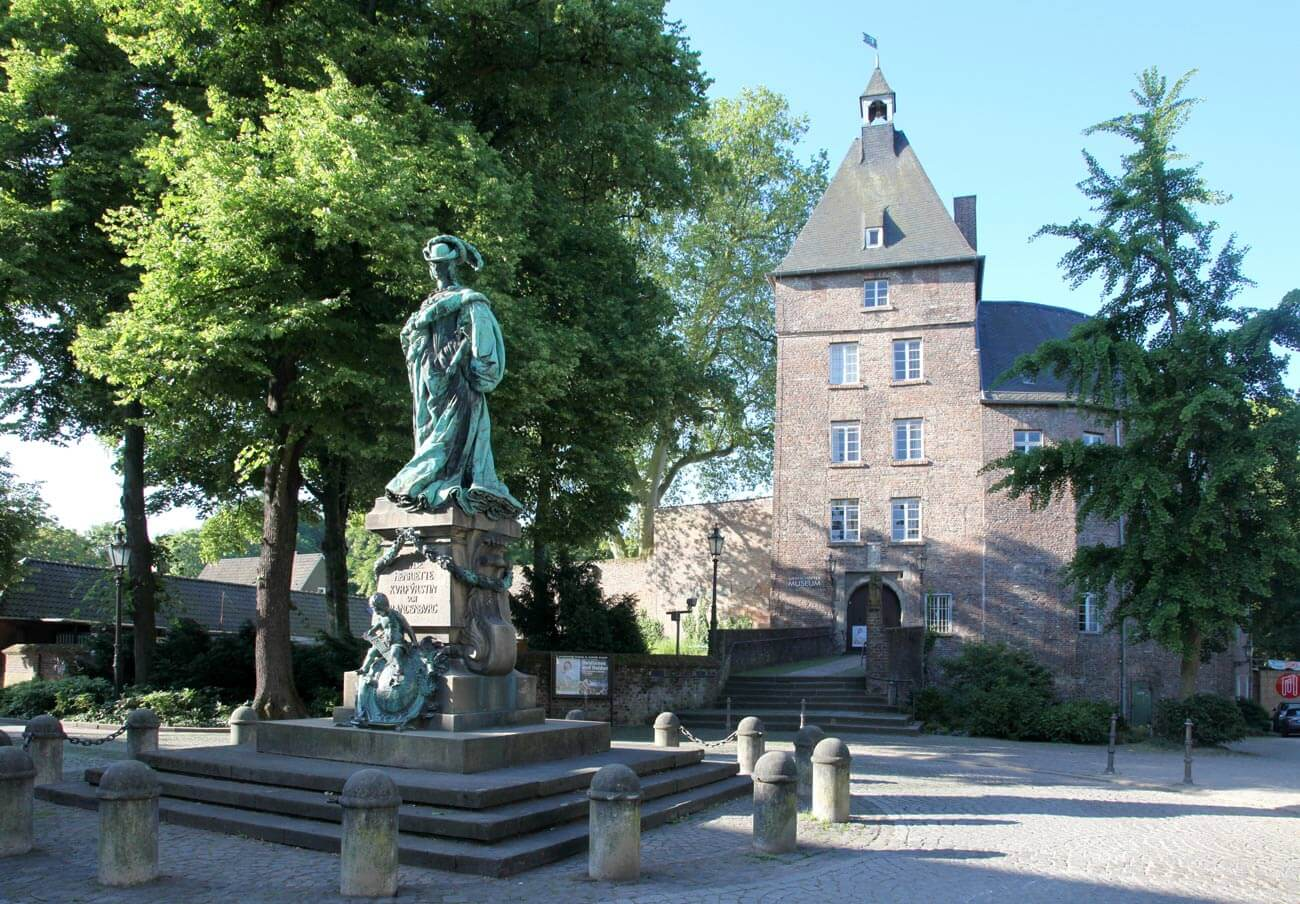 as Foto zeigt das Moerser Schloss mit dem Grafschafter Museum. Vor dem Schloss steht die Statue von Luise Henriette von Oranien.