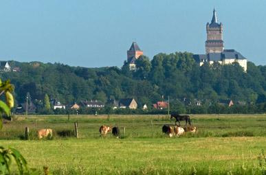 Aussicht über grüne Felder bis zur Schwanenburg in Kleve auf der der Oranier-Fahrradroute von Lingen über Apeldoorn nach Moers